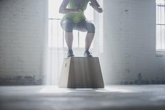 Athlete crouching on platform in gym Stock Photos