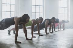 Athletes doing push-ups in gym Stock Photos