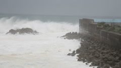 Strong waves crashing against barrier wall during storm - stock footage