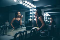 Black woman applying makeup in vanity mirror Stock Photos