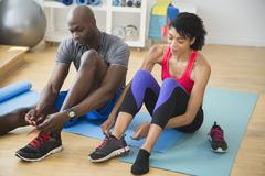 Couple tying sneakers in gym Stock Photos