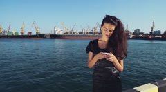 elegant business lady uses mobile internet on the smartphone in the seaport - stock footage