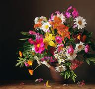 Bouquet from cultivated flowers against a dark background - stock photo
