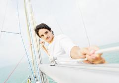 Hispanic man adjusting rigging on sailboat Stock Photos
