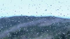 Water droplets movement on glass with mountain view blur and rain in background Stock Footage