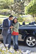 Couple walking in driveway at convertible Stock Photos