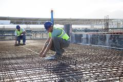 Construction workers arranging rebar at construction site Stock Photos