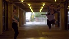 2 Dancers Leap Continuously Toward Camera Through A Tunnel In City (Slow Motion) Stock Footage