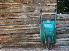 Old aged wheelbarrow on wooden wall Stock Photos
