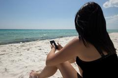 Girl Texting at the Beach Stock Photos