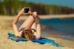 Summer vacation Girl with phone tanning on beach - stock photo