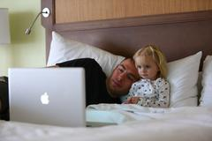 Little girl is watching cartoon with dad while sick. - stock photo