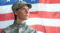 A female soldier standing in front of an american flag Stock Footage