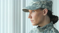 A female soldier looking out a window and then at the camera Stock Footage