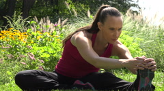 Female runner stretching and touching her toes Stock Footage