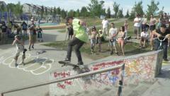 Skateboarder grinds curb at skate park Stock Footage