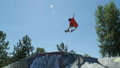 Skateboarder does big air grab off of quarter pipe Stock Footage