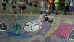 Skateboarder cruises around the bowl slow motion. Stock Footage