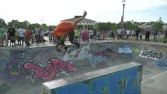 Skateboarder does a 180 in the air off of ramp in bowl. Stock Footage