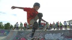 Skateboarder jumps out of bowl, stalls tail of board on edge then drops back in. Stock Footage
