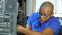 Technician working on computer/server, wide shot Stock Footage