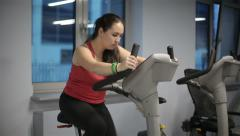 Fat woman at the gym on an exercise bike Stock Footage