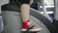 Close up woman's legs in red sneakers on bike simulator at the gym Stock Footage