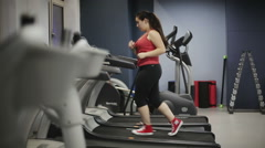 Fat female teenager on treadmill in gym - stock footage