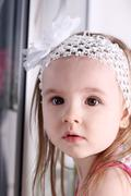 Closeup of face of cute little blond girl with white headband Stock Photos