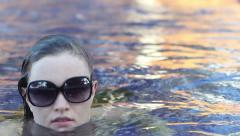 Brunette Wearing Sunglasses and a Strapless Costume Rolls Over in the Water Stock Footage