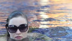 Brunette Wearing Sunglasses and a Strapless Bathing Suit Rolls Over in the Water Stock Footage