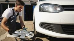 Tire service: Man loosening the screw on a tire - stock footage