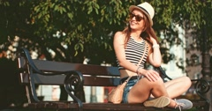 Woman smiling and sitting on a bench in European city. Slow Motion. Stock Footage