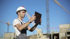Сonstruction engineer with the tablet pictures of objects - stock footage