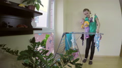 Mother take clean baby clothes from dryer, hold child on arm. 4K Stock Footage