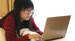 Asian Woman wearing glasses lying on a bed at home and she works on a laptop Stock Footage