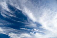 Wide view of blue sky with spreading cirrus clouds - stock photo