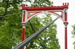 Retro style bridge in the rain, selective focus on steel ropes bundle Stock Photos