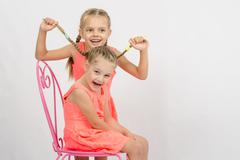 Stock Photo of Girl having fun with pigtails sister