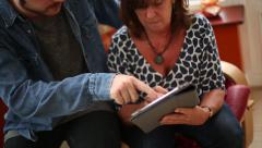 Young Man Teaches Mother How to use Tablet Stock Footage