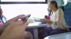 4k Close up on hands of young man using a smartphone on train journey Stock Footage