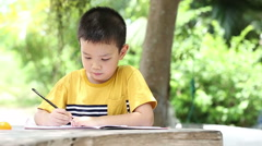 Little asian boy use pencil writing on notebook for writing book Stock Footage