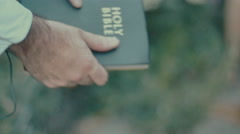 Walking by with bible cinematic Stock Footage