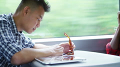 4k Young Asian man texting on phone on train journey with friends Stock Footage