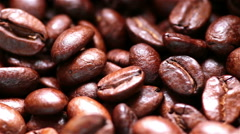Coffee beans falling out of a roaster, macro sliding shot Stock Footage