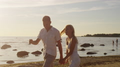 Couple Having Fun on the Beach. Man Carrying Girl in his Arms and Whirling - stock footage