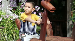 Asian kid playing on the wooden rocking Horse Stock Footage