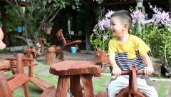 asian kid playing on the wooden rocking Horse - stock footage