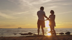 Girl and Man Having Fun Together on the Beach. Holding Hands and Whirling Stock Footage