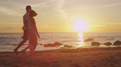 Girl and Man Having Fun Together on the Beach. Holding Hands and Whirling - stock footage